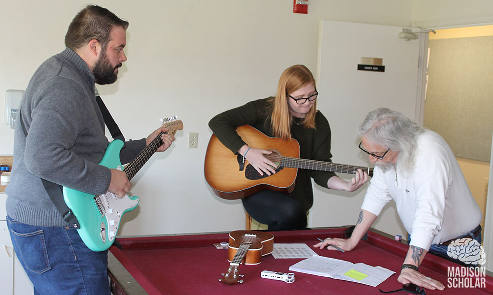 a professor and a student with guitars work with a Gemeinschaft resident around a red pool table.