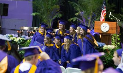 group of seniors in purple cap-and-gown posing for group photo