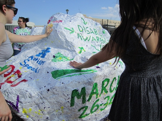 Spirit Rock decorating event, students placing hand prints on rock.