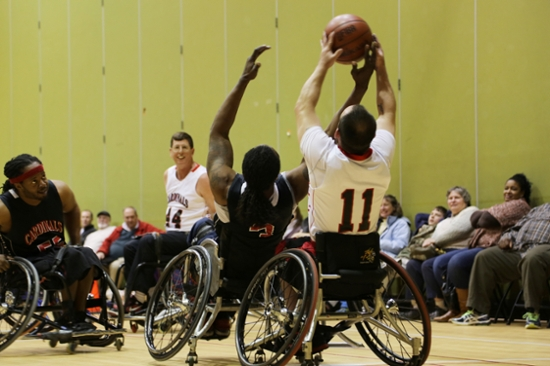 Four basketball players in wheelchairs. Number 3 is trying to steal the ball from Number 11.