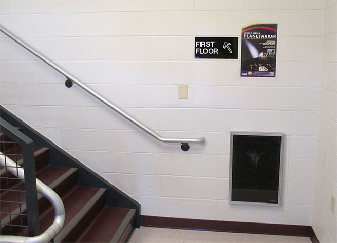 Planetarium poster is on the wall to the right of the stairs visitors need to use.