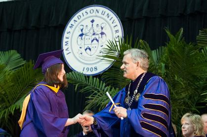 President Alger shaking hands and giving a diploma to a Class of 2012 graduate