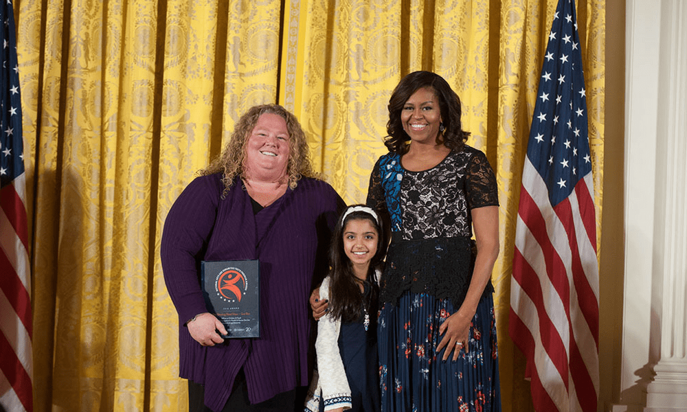 Kim Hartzler-Weakley and Sarah Hussein pose with then-First Lady Michelle Obama at a White House ceremony recognizing the Gus Bus.