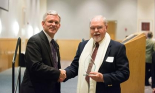 JMU President Jonathan Alger shakes hands with Harold Huber upon presenting him with the Community Service Award from the Mahatma Gandhi Center for Global Nonviolence. Huber accepted the award on behalf of his late wife, Dr. Vida Huber.