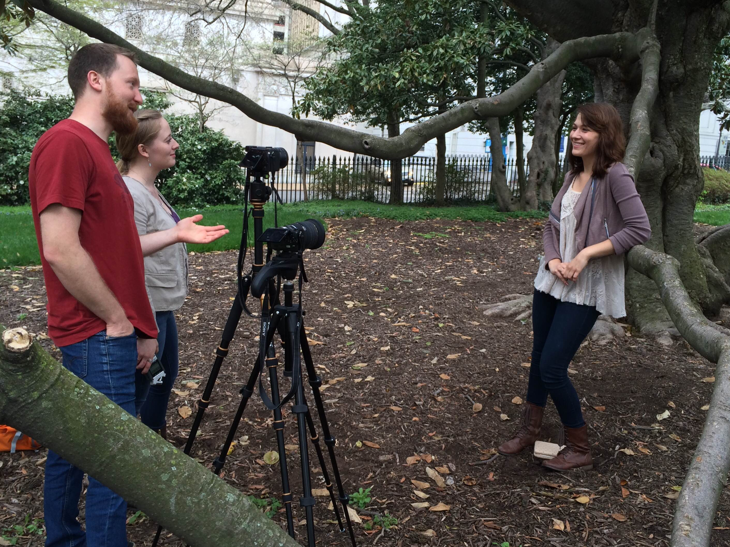 Student film team interviewing source outdoors.