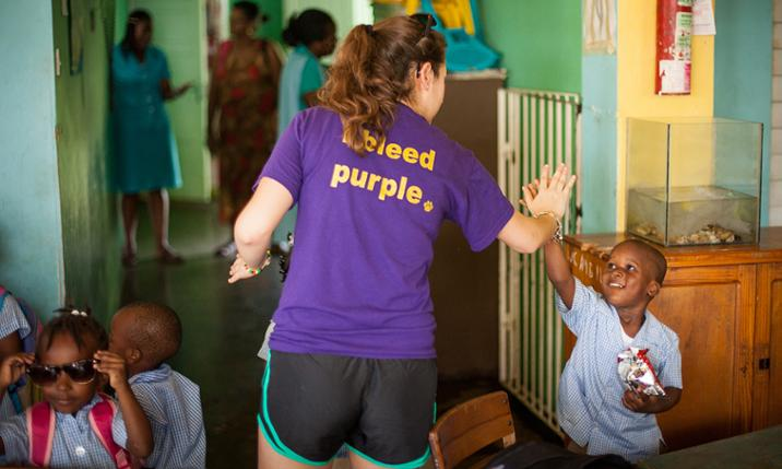 JMU student and children at CUMI during Alternative Spring Break trip to Jamaica