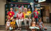 Photo of Fred and Gail Fox and community children at One World exhibit