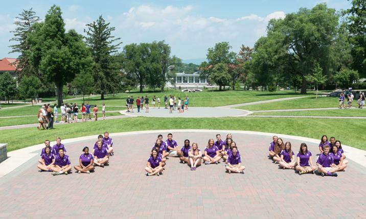 Photo of First Year Orientation Guides posing as the letters JMU on Quad