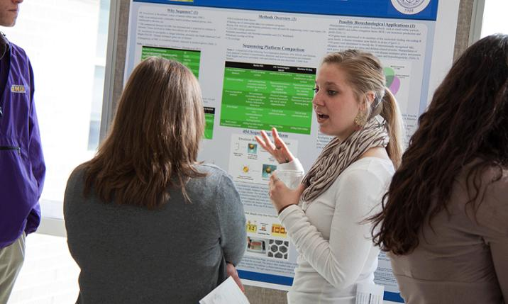 Photo of JMU students presenting research at Genome Project poster session