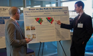 Prince (right) shares research on the Bosnian War during the poster presentation at the War to Peace conference at JMU.
