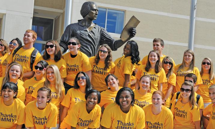 Photo of JMU students wearing Thanks Jimmy t-shirts next to statue of James Madison