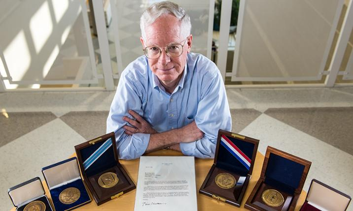 Dr. Tim Walton with a display of some of his achievement awards