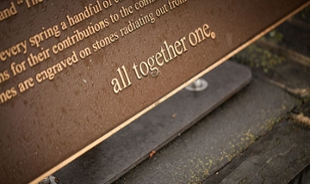 A close-up photo of the All Together One plaque is on the JMU Commons.