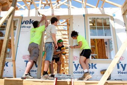 A group of young men and women work on framing a house.
