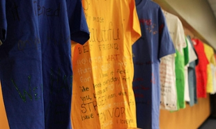 A row of t-shirts on dispaly.  The t-shirts have hand-written messages on them.