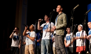 Young men singing on stage at JMU Wilson Hall