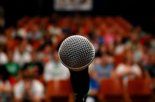 Picture of an open mic in front of an audience