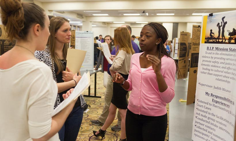 A JMU Psychology graduate student discusses her practicum experiences at a poster presentation