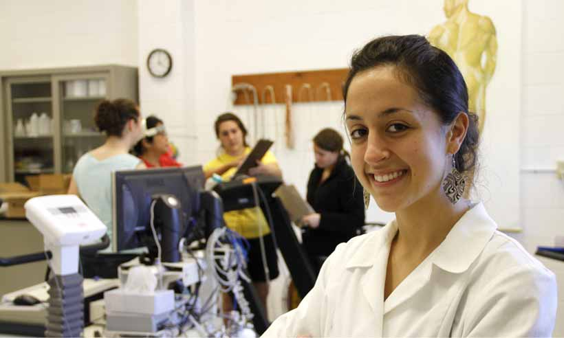 A student in a white lab coat in a Kinesiology lab