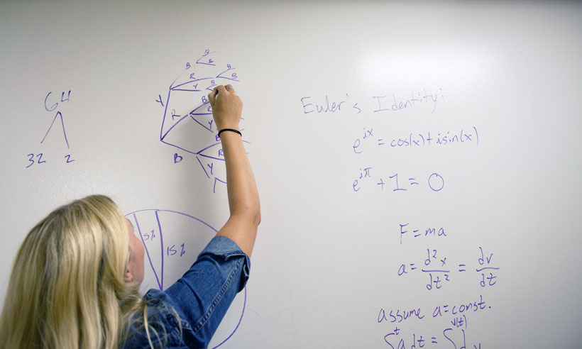 A JMU student solves a math problem at a white board