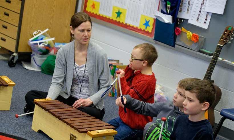 A student teacher works with children in a music class