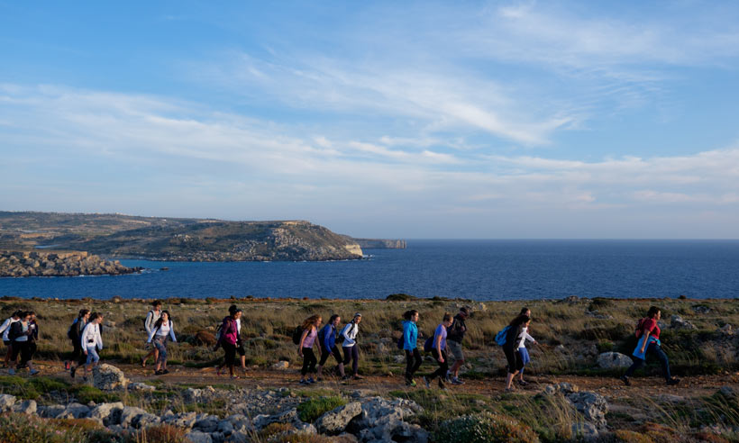 Students abroad hiking in front of ocean