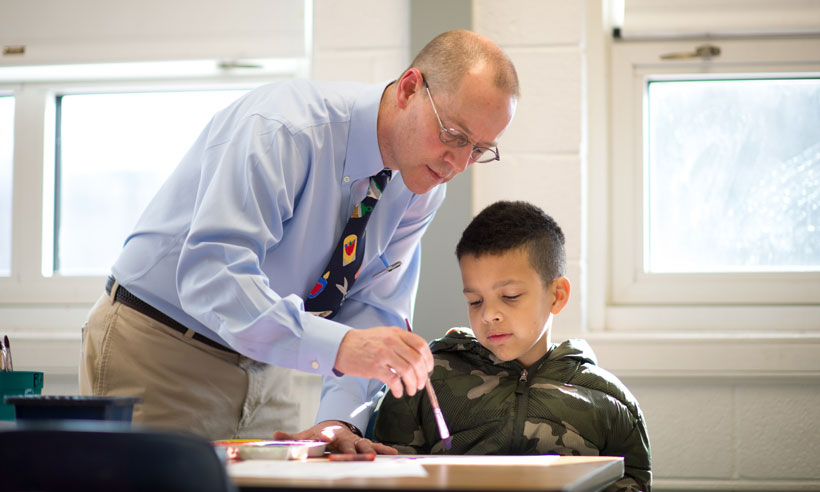 A student teacher works with a child