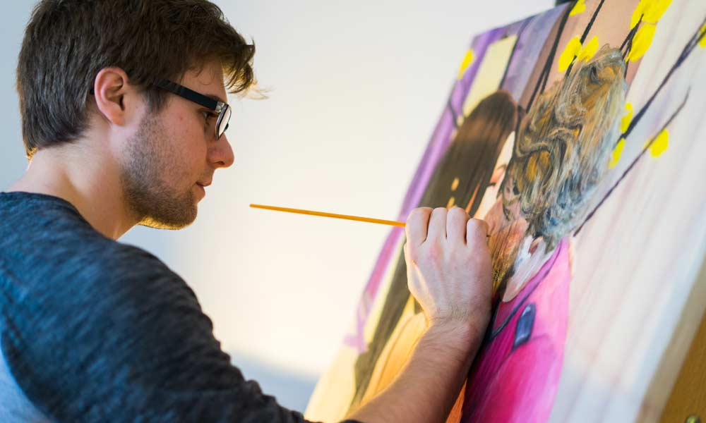 Studio art student Nathaniel St. Amour painting