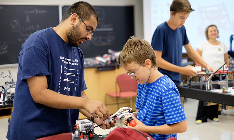Student teaching robotics class