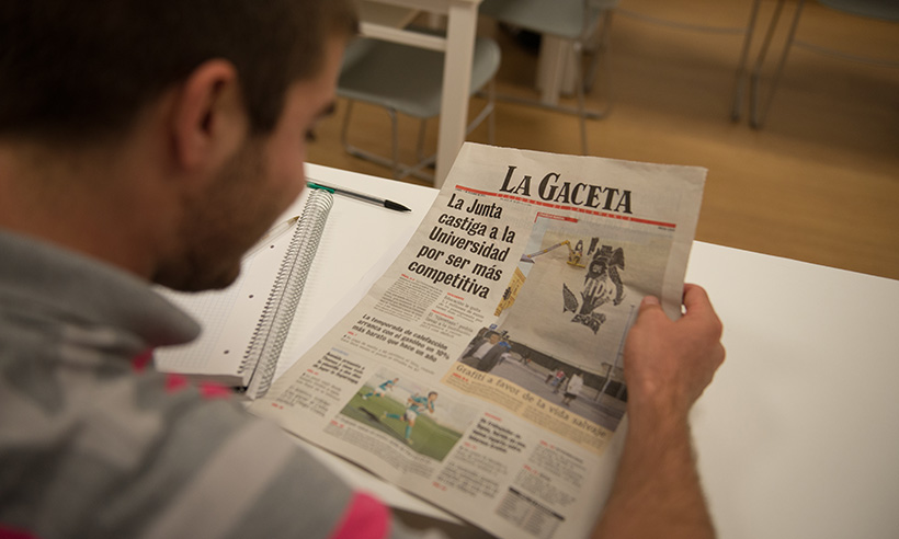 Male student reading Spanish newspaper