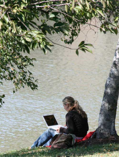 Student using laptop by Lake Newman