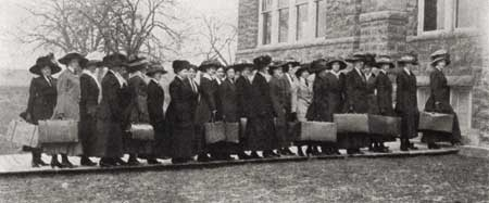 Freshman ladies of 1910 line up with their suitcases.