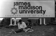 Students sitting in front of a 1970's James Madison University sign