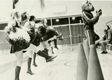 Early version of Duke Dog helps cheerleaders lead cheers.
