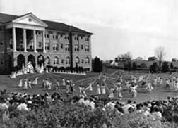 A large crowd and the May Queen and her Court gather in front of Converse Hall to watch several simulaneous Maypole dances in 1936.