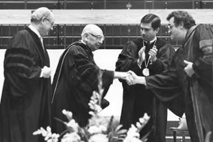 At JMU's 75th anniversary celebration in 1983, two of the university's first three honorary doctorate recipients - Wallace L. Chandler (left) and former Virginia Gov. Charles S. Robb - look on as JMU's fourth president, Ronald E. Carrier (right), shakes hands with the third president, G. Tyler Miller.