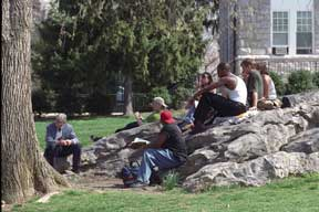 Male students on the Rock listening to a professor