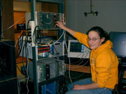 JMU student sitting in front of a rack of electronic equipment.