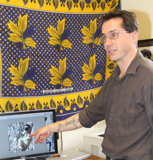 Dr. Richard Lawler points to a photo of a lemur on his computer in his office