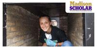 JMU student crouches inside biochar chamber.