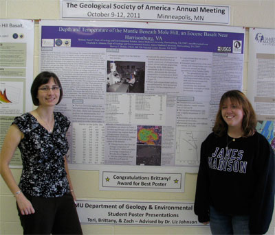 Brittany Sacco and Liz Johnson stand in front of the award winning poster