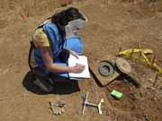 Daniele Ressler writing data on a pad in a Jordanian minefield