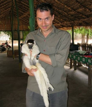 Richard Lawler holds a lemur.