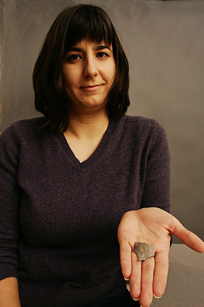Julie Solometo holds out a sharp-edged fragment of a projectile in the palm of her hand.