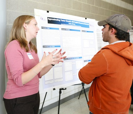 A student presents her poster.