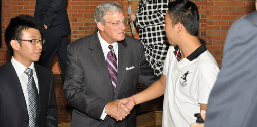 President Rose shakes hand of an international student at ceremony
