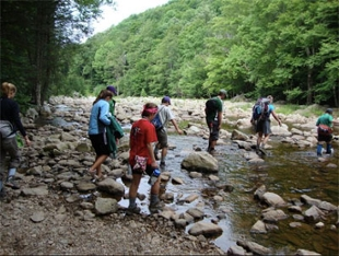 students on adventure trip cross a creek