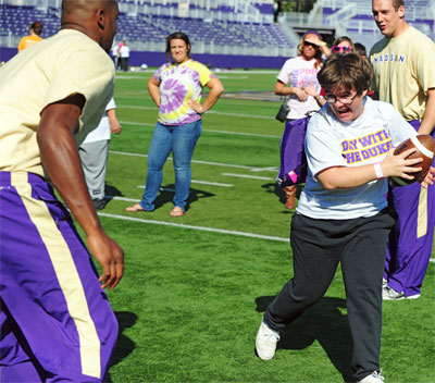 Special Olympian enjoys playing football during Day With The Dukes at Bridgeforth Stadium.