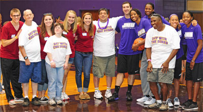 Special olympians pose with JMU basketball players for a group shot during Day With The Dukes.