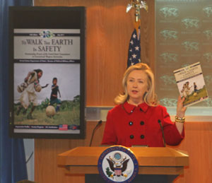 Hillary Rodham Clinton holds magazine during press conference.